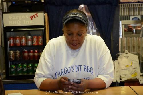 Belinda of Fargo's Pit BBQ holding a Manic Card.