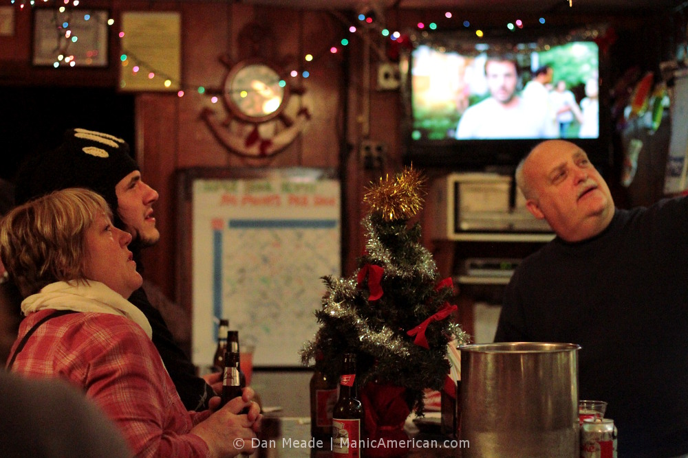 Nothing seperates this bartender from his patrons, except for a Christmas tree.