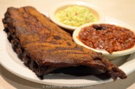 A plate of smoked pork ribs covered with dry rub, accompanied by side dishes of beans and slaw