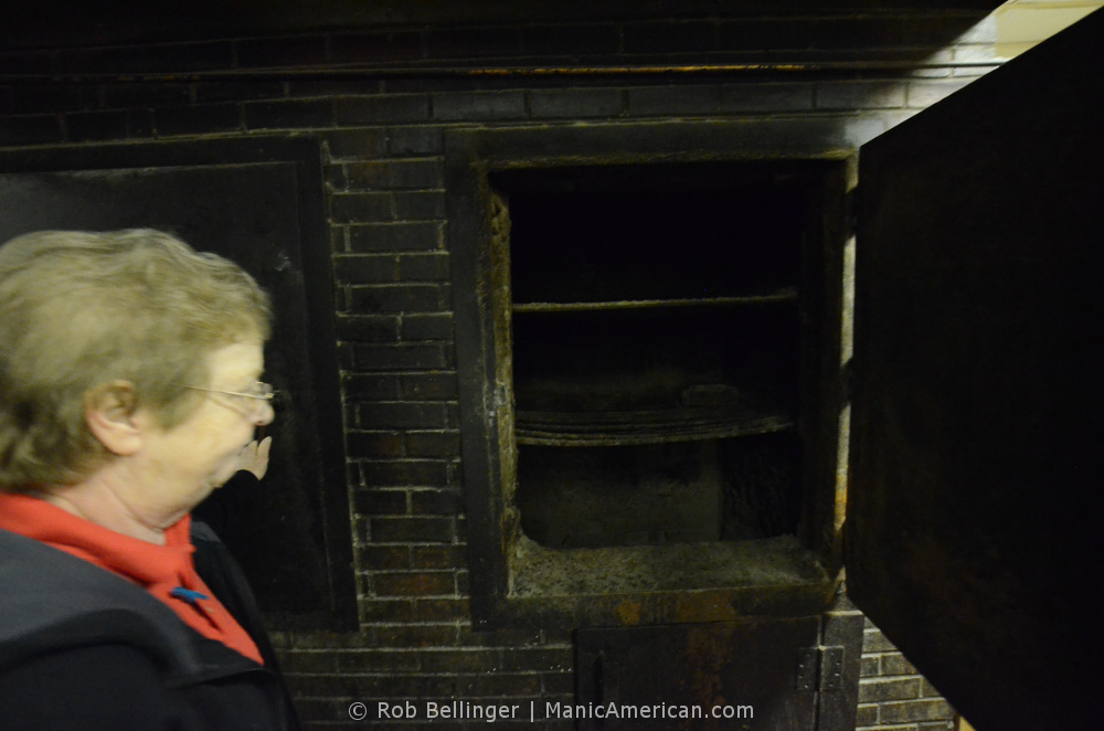 An employee opens up the brick charcoal pit the restaurant used for decades