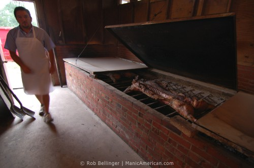 A hog smoking over hickory coals as a worker walks by