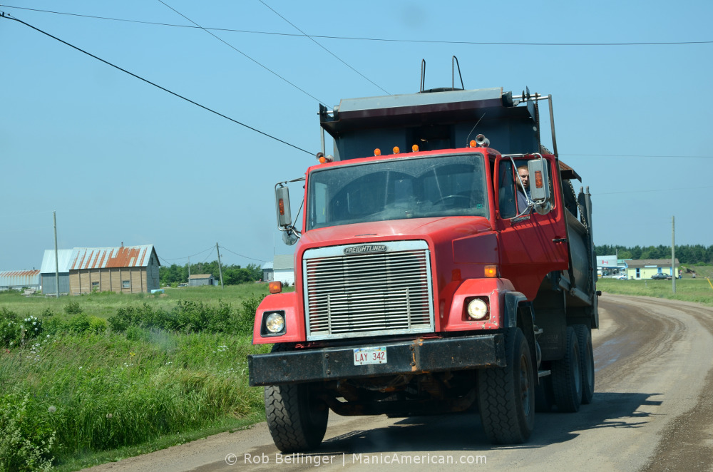 A dusty dump truck. The driver is standing outside the cab to see where he is going.