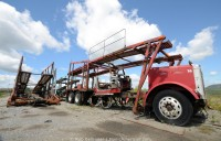 An abandoned car carrier truck, missing its cab, sits under a blue sky. Corner Brook, Newfoundland.