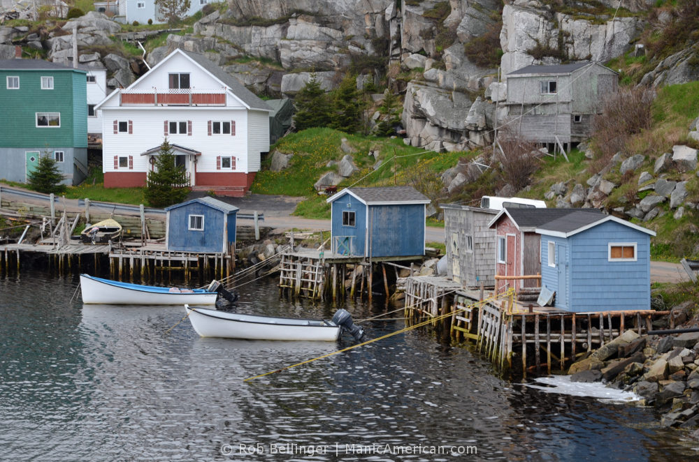 Motor skiffs are tied up to fishing docks nestled among craggy cliffs. Rose Blanche-Harbour le Cou, Newfoundland.