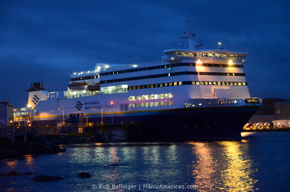A large ferryboat is moored at night, with lights shining out over the water. Port aux Basques, Newfoundland.