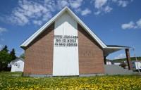 A brick church in a field of daffodils. Corner Brook, Newfoundland.