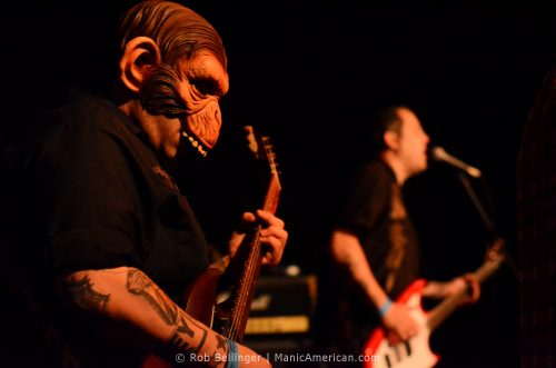 a guitarist wearing an alien ape mask
