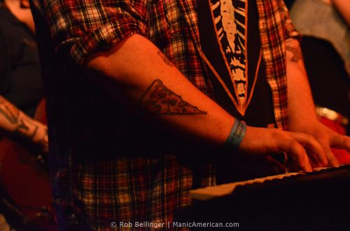 a pizza slice tattoo on the forearm of a keyboard player