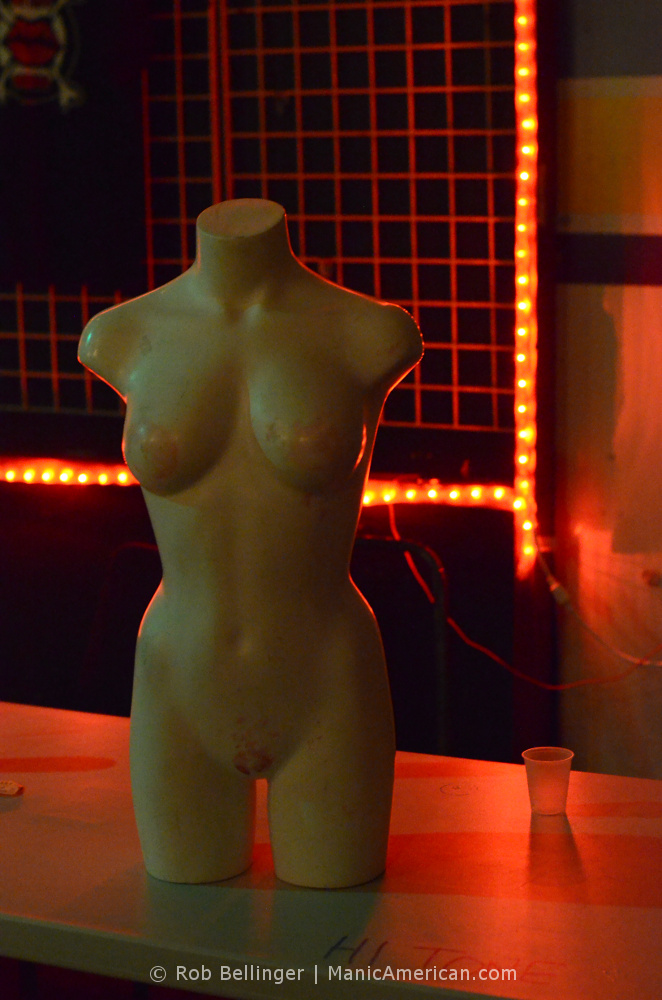 a nude female mannequin on a table with red lights in the background