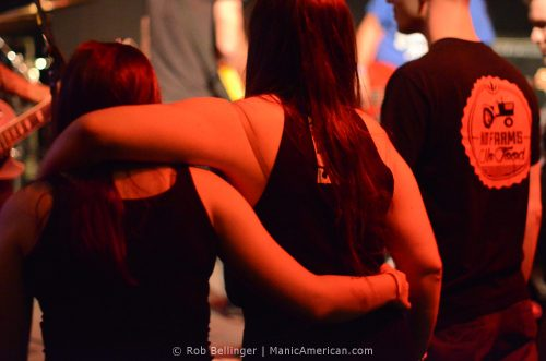 women at a punk show standing arm in arm