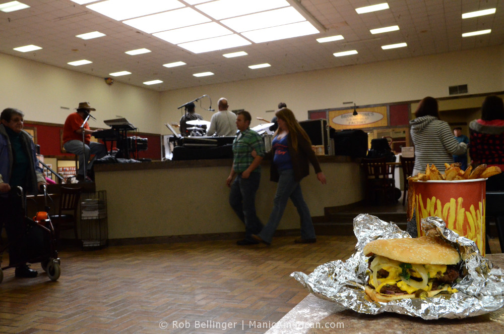A cheeseburger on aluminum foil sits next to french fries on a table, while shoppers in a mall listen to a band playing in the background