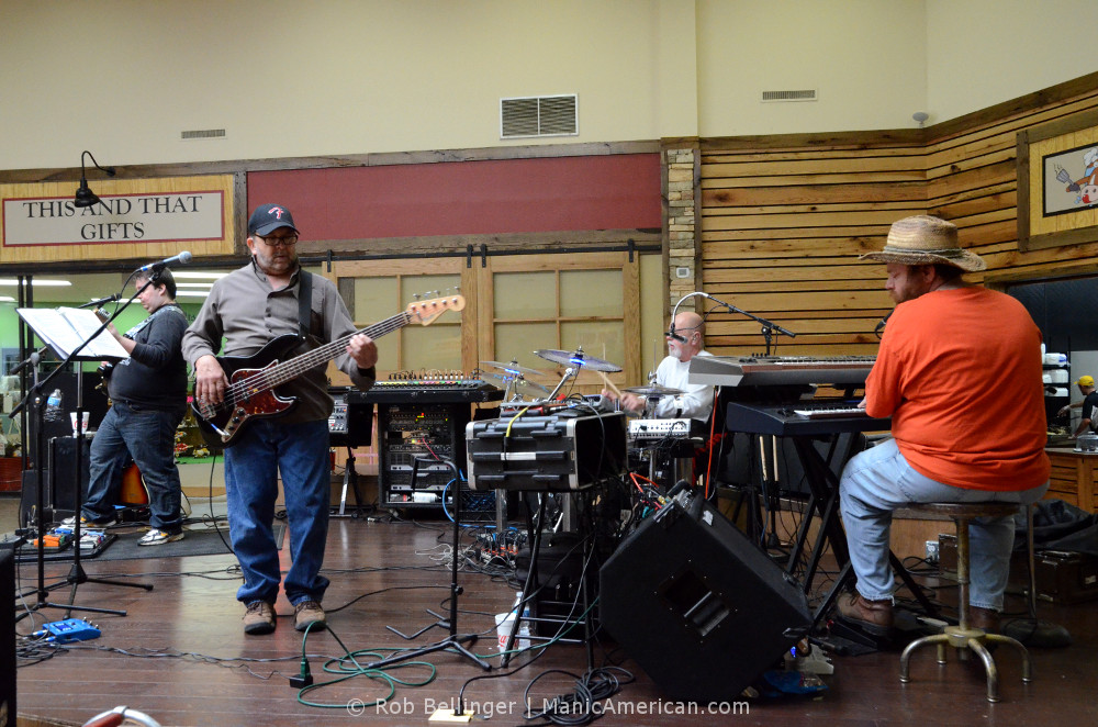 A band of four middle-aged musicians plays rock music in the dining area of a mall.