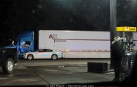 A cowboy wipes his windshield as a police officer approaches a big rig