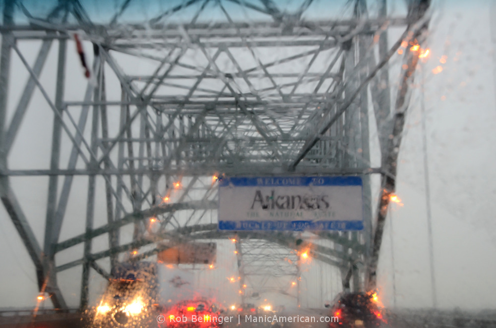 View through the windshield of a car, in heavy rain and gray skies, at the Welcome to Arkansas sign in the middle of the Hernando de Soto Bridge over the Mississippi River