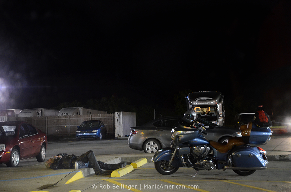 At a rural truck stop in the middle of the night, a middle-aged biker lies on the pavement, inhaling through a lit cigarette near his blue motorcyle