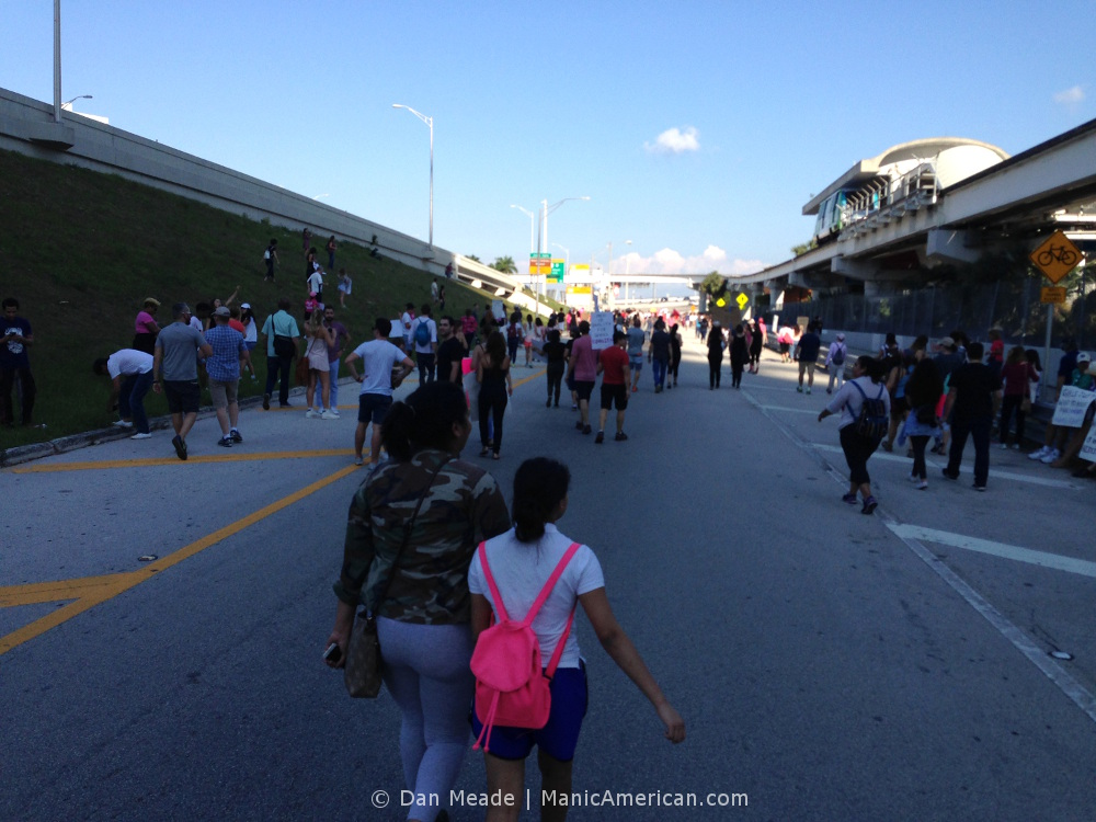 A woman and child march toward 395