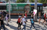 Marchers pass a tounge-in-cheeck bus ad