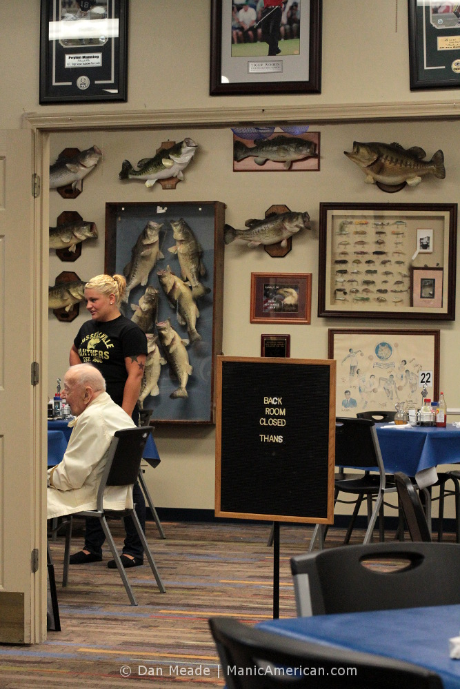 A waitress takes orders behind a wall of trophy fish.