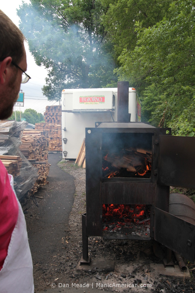 Making Kentucky barbecue: The coalmaster watches as wood burns down to coals.