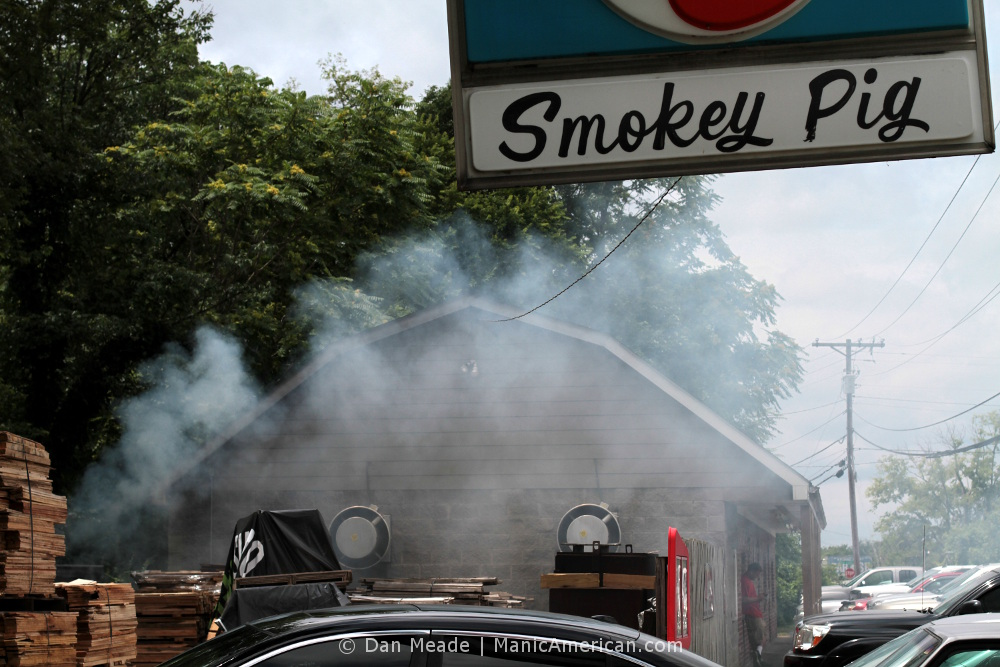 An employee takes a break behind a cloud of smoke outside the Smokey Pig, a Kentucky barbecue restaurant.