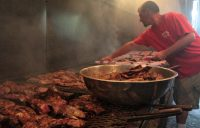 Making Kentucky barbecue: Pork shoulders and other cuts are placed above a bed of coals.