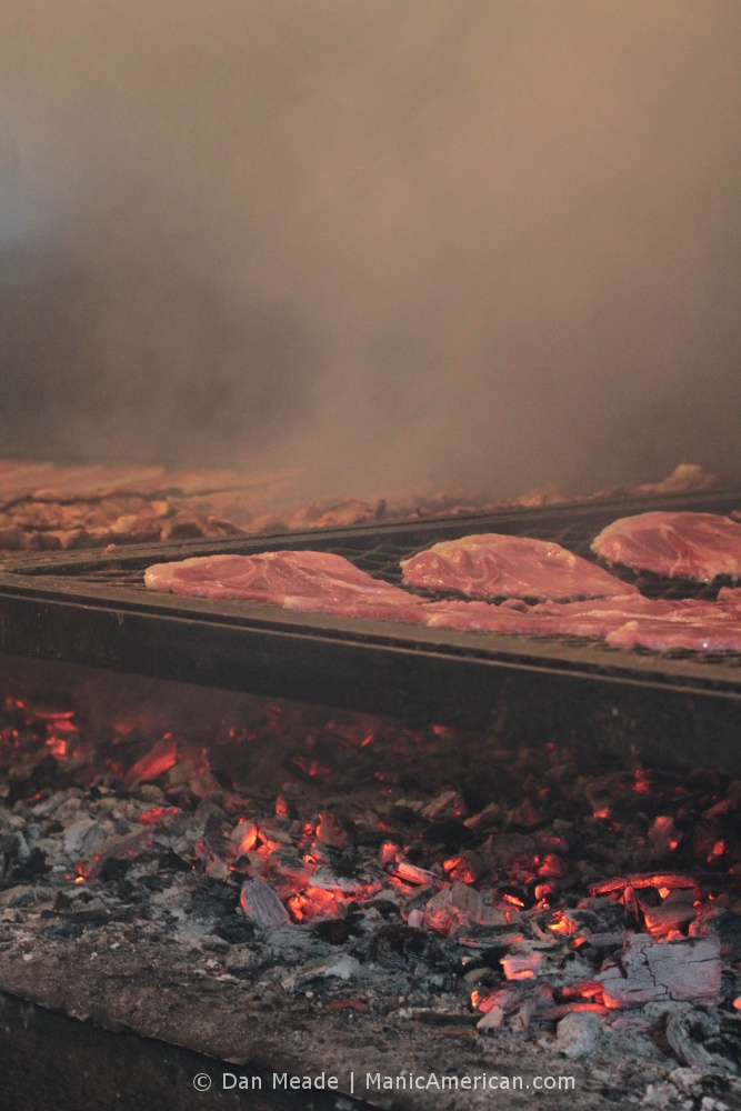 Making Kentucky barbecue: Slices of pork shoulder cook over a bed of coals.