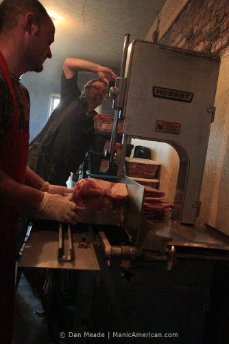 Wes Berry photographs a pork shoulder being sliced.