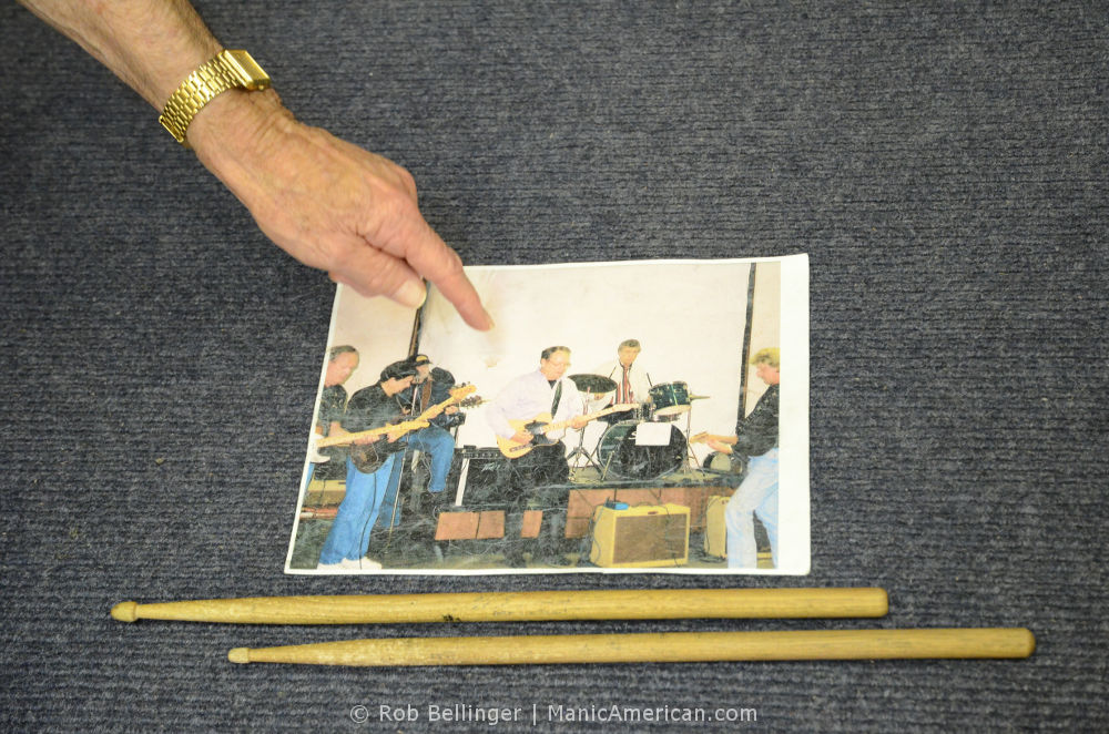 A hand, wearing a gold watch, points to a photo of musicians in the recording studio. Two drumsticks sit next to the photo.