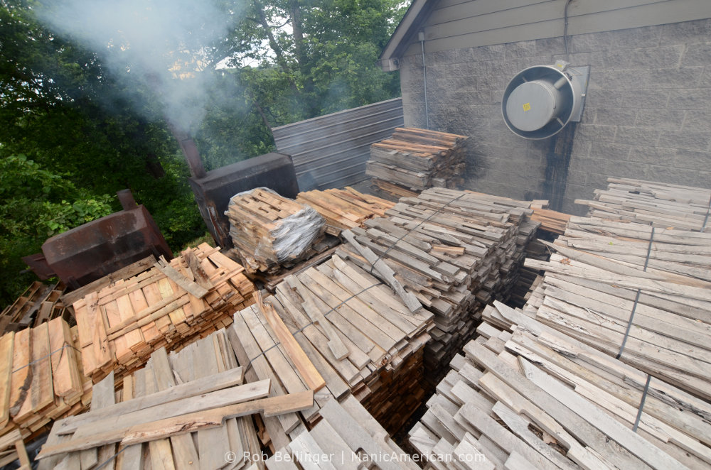 Outside a cinder block building, pallets of hickory boards sit while smoke billows from a steel cauldron in the background