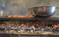 Hickory coals burn and glow under a steel grill and stainless steel bowl to make Kentucky barbecue