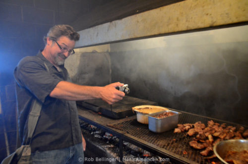 Professor Wes Berry in the Smokey Pig cookhouse, using a point-and-shoot camera to photograph the grill