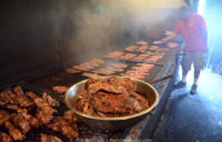 Making Kentucky barbecue: In the foreground, a bowl of cooked pork shoulder. In the background, a man putting raw pork shoulder on the grill.