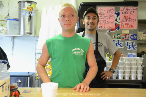 Two employees stand at the front counter of the Smokey Pig Kentucky barbecue restaurant during lunch rush