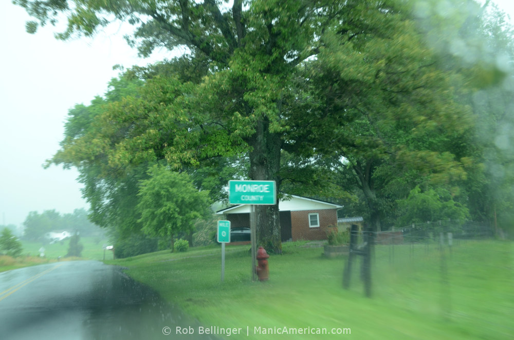 A rainy country road with a sign marking Monroe County