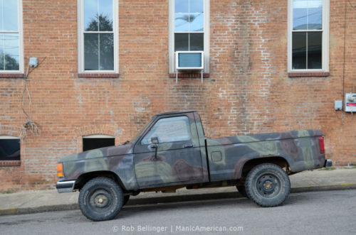 A small pickup painted with military-style camoflauge parked on a hill in front of a brick building