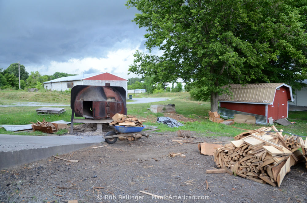 A backyard lot with a pile of hickory logs, a wheelbarrow full of logs, and a steel furnace. In the distance, dark rain clouds are forming.