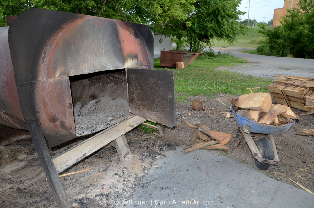 A round, steel furnace with its door open. Next to it is a wheelbarrow filled with hickory logs behind R&S BBQ in Tompkinsville, Kentucky.