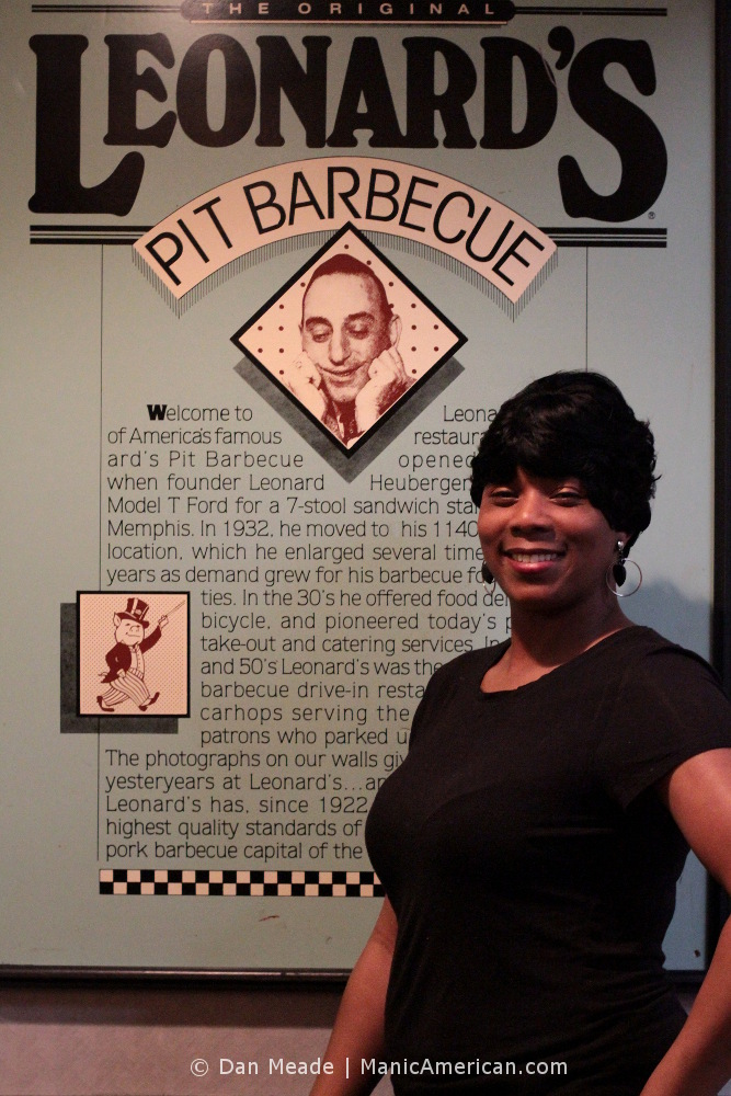 Angie stands before a sign bearing Leonard's history.