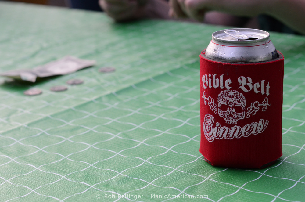 A cold beer can in a koozie with a skull on a picnic tablecloth, with gambling money in the background.