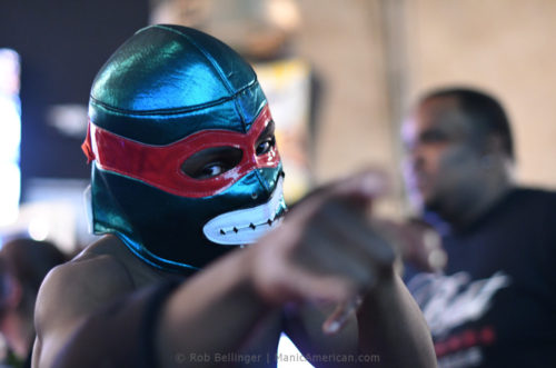 A shirtless man in a ninja turtle mask points into the crowd