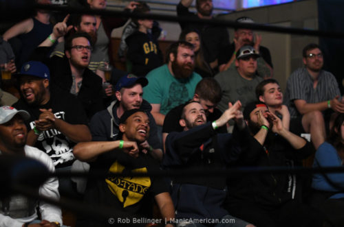 Framed by the ropes of the wrestling ring, a crowd of mostly young men cheers on the wrestlers.