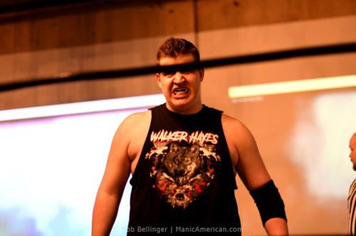 With the top rope blocking the view of his eyes, Walker Hayes steps into the ring wearing a shirt showing his name in heavy metal font and a wolf surrounded by bloody bones.