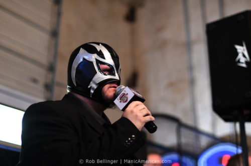 A man wearing a full-face lucha libre mask uses a microphone to announce the fight