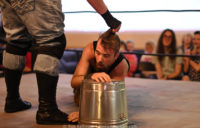Sam Armstrong, holding onto a metal bucket, is dragged upward by his hair