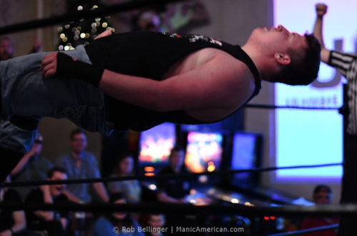 Walker Hayes falls to the mat, seen between the ropes of the ring, parallel to the floor