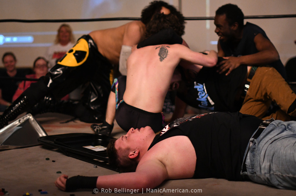 Three wrestlers help Sam Armstrong up after Walker Hayes is defeated. Hayes lies on the mat surrounded by Legos and a folding chair.