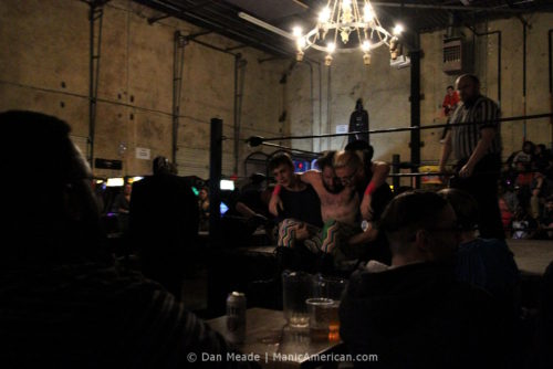 A defeated wrestler is carried from the ring