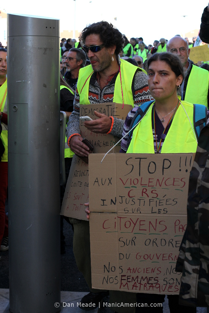 Placard wearing gilets jaunes protestors.