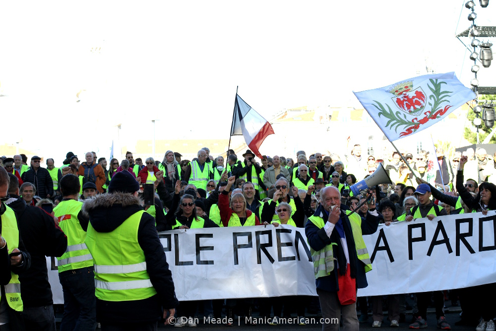 A mass of gilets jaunes protestors with flags and banner.