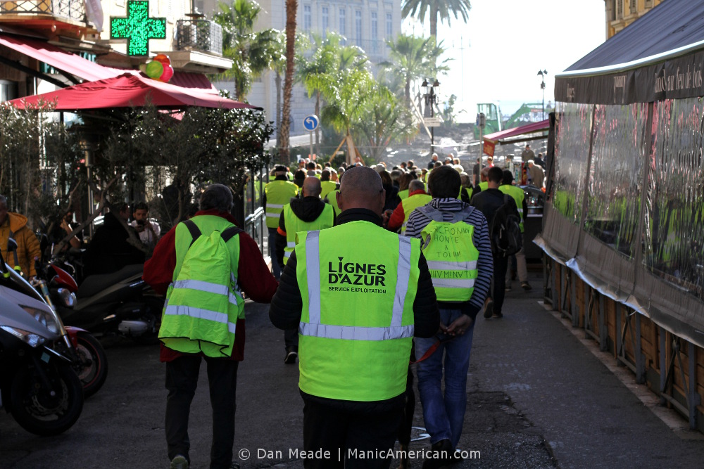 Three giletes jaunes protestors walk away from the camera.